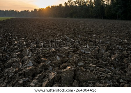 Newly ploughed field in spring time during sunset. Conceptual of farming and agriculture. - stock photo
