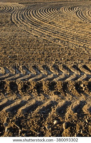 Newly plowed patterned clay soil farm field on sunny day - stock photo