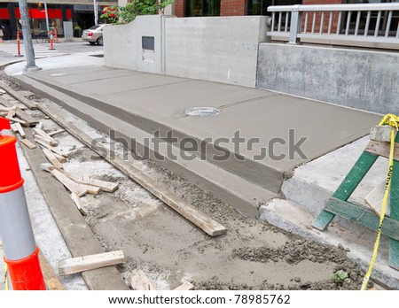 Newly poured cement on urban sidewalk - stock photo