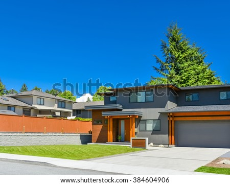 Newly renovated family house in Vancouver, British Columbia. Residential house with wide garage door and concrete driveway. - stock photo