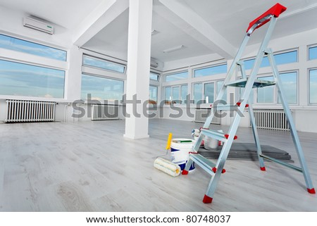 Newly renovated generic empty office space with leftover materials and ladder in foreground - stock photo