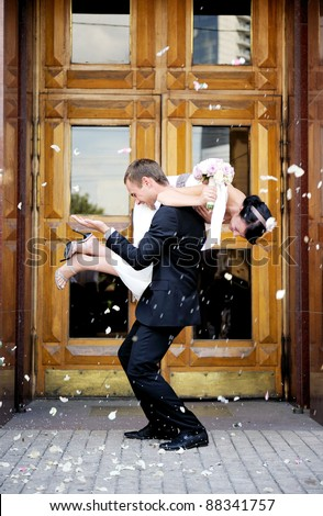 Newly wed couple being showered in rose petals - stock photo