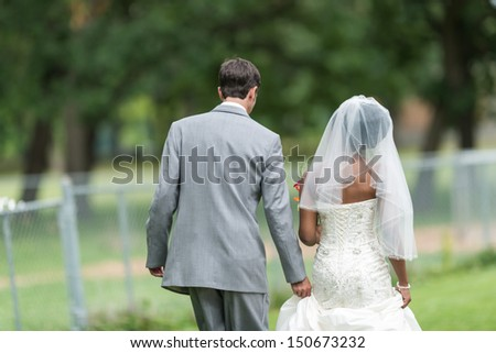 Newly wed interracial couple walking away
