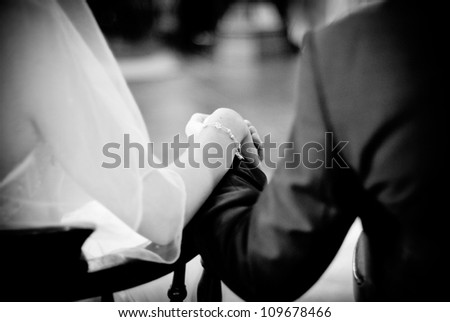 Newly wedded holding hands during church ceremony. - stock photo
