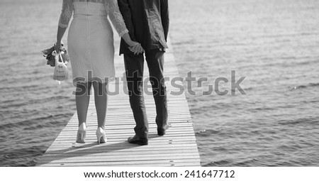 Newlywed caucasian couple walking together at pier.