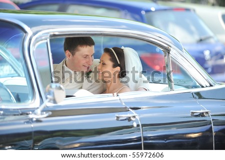 newlywed couple, groom  and bride,  in car - stock photo
