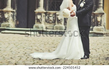 Newlywed couple holding hands. Spending happy wedding day together.  - stock photo