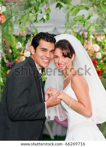 Newlywed couple smiling for the camera - stock photo