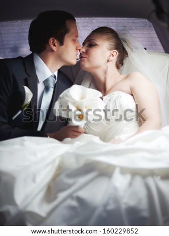 Newlywed young couple in limo kissing. Wedding picture.