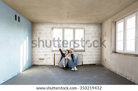 Newlyweds build your new home. Woman and man sitting on the floor and planning. - stock photo