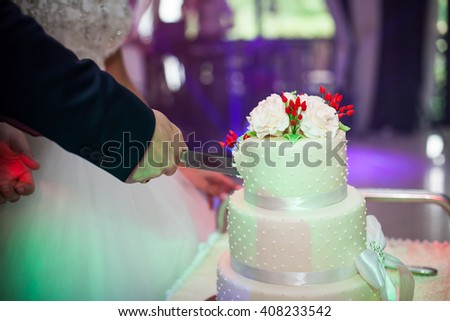 Newlyweds carving a delicious tiered white wedding cake decorated with roses and a ribbon closeup - stock photo