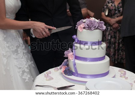 Newlyweds carving delicious white wedding cake with purple roses frosting - stock photo