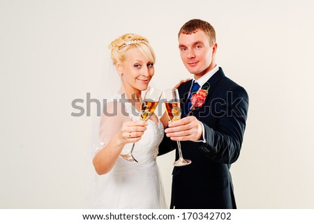 newlyweds embracing and kissing. Cute young married couple posing on white background. Bridal happy couple isolated on white background.  Bouquet of flowers, wedding dress