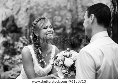Newlyweds. Groom gives bouquet to bride the greenhouse. - stock photo