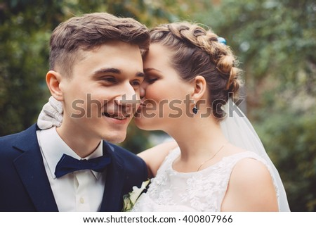 Newlyweds in love. The color photo of bride and groom are walking together in a park. The bride is kissing a groom. Bride is smiling with pleasure. Couple became husband and wife this day. - stock photo