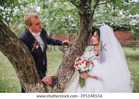 newlyweds in park.newlyweds on walk in the beautiful wood.newlyweds embrace.embraces of newlyweds.newlyweds in the spring wood.gentle.relations.feelings.beautiful groom and bride.fantastic wedding.