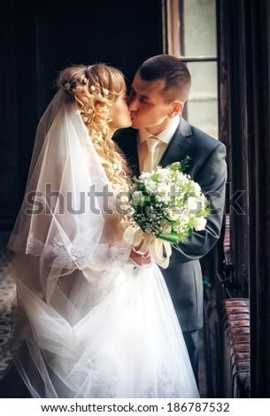 Newlyweds kissing near the window  - stock photo