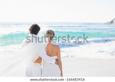 Newlyweds looking out to sea together at the beach - stock photo