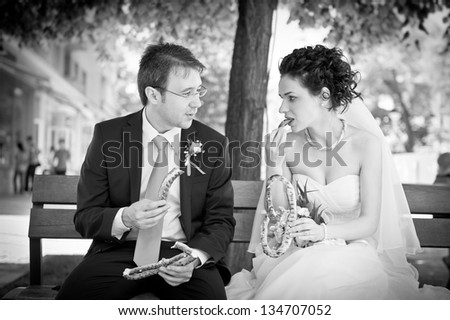 Newlyweds on the bench in park and eating pretzels .Just married sitting on the bench and eating pretzels