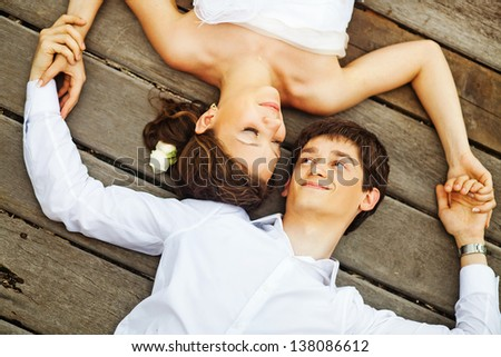 newlyweds on the floor (focus on the eyes of bride) - stock photo