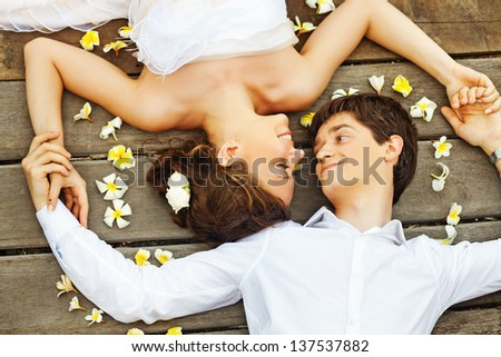 newlyweds on the floor (soft focus on the bride's eyes) - stock photo