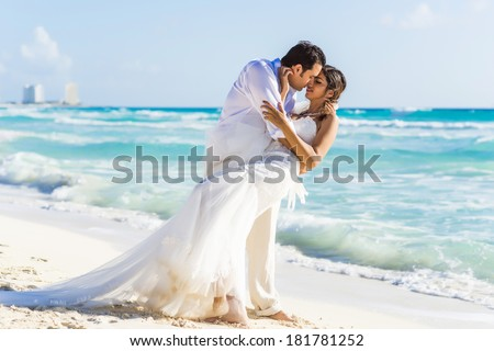 Newlyweds  sharing a romantic moment at the beach - stock photo