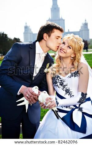 Newlyweds with pigeons on the wedding walk. Romantic kiss. - stock photo