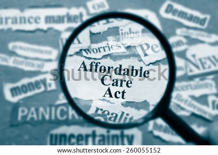 News headlines and magnifying glass with Affordable Care Act text - stock photo