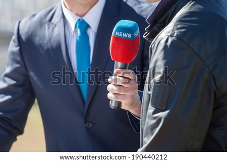 news journalist with microphone interviewing - stock photo