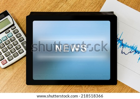 news word on digital tablet with calculator and financial graph - stock photo