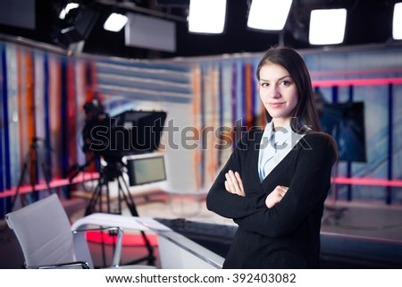 News writing and reporting.Woman journalist in television studio standing with her arms crossed.Determination,journalistic fairness and accuracy.Interview talk show with live audience.Media industry - stock photo