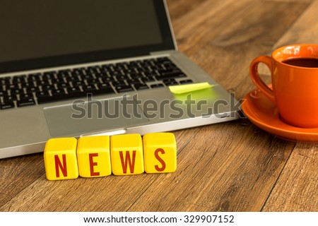 News written on a wooden cube in front of a laptop - stock photo