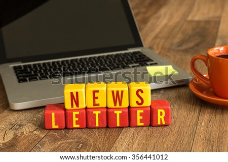 NewsLetter written on a wooden cube in a office desk - stock photo