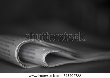 Newspaper against plain background with shallow depth of field - stock photo