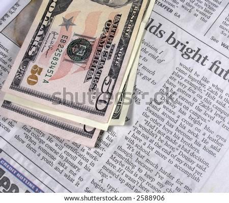 Newspaper and dollars - stock photo