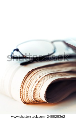 newspaper and glasses on white background - stock photo