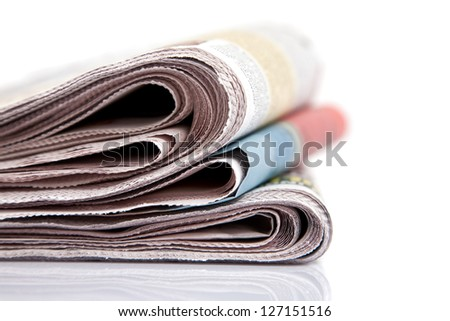 newspaper close up on white background, shallow - stock photo