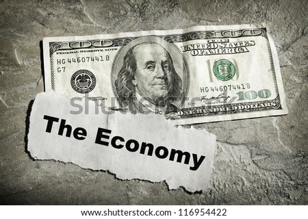 Newspaper headline with Economy text and cash - stock photo