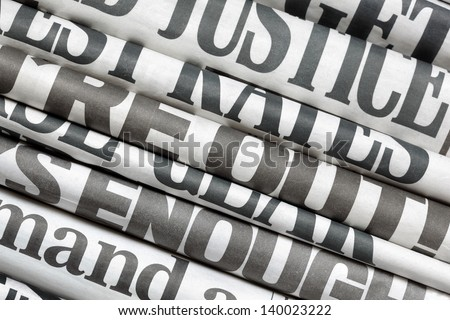 Newspaper headlines side on in a stack of daily newspapers - stock photo