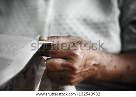 newspaper in the hand of  old woman - stock photo