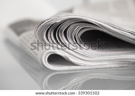 Newspaper mirrored on glass table against plain background with shallow depth of field - stock photo