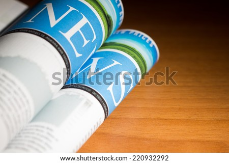 Newspaper on the table with very shallow depth of field. -Custom Design newspaper. - stock photo
