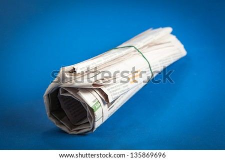 Newspaper roll on a blue background - stock photo