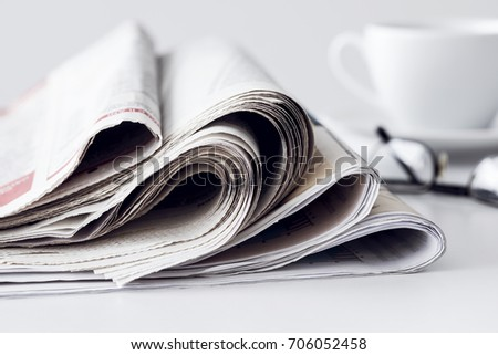 Newspaper with a cup of coffee on table