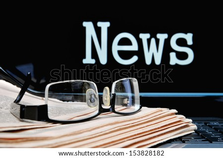 Newspaper with glasses below the laptop monitor lettering news - stock photo