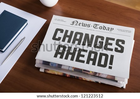 "Newspaper with hot topic ""Changes Ahead"" lying on office desk. - stock photo"