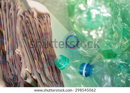 Newspapers and empty bottles collected for recycling - stock photo