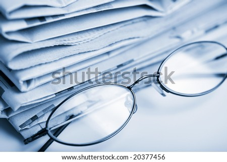 newspapers and glasses toned blue - stock photo