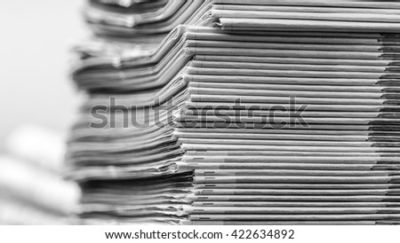 Newspapers folded and stacked concept for contact, communication, publication, pile of newspapers shallow depth of field background image black and white horizontal photography - stock photo
