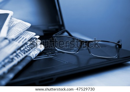 Newspapers laptop glasses in composition blue toned - stock photo
